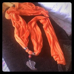 Orange scarf with leaf pendant